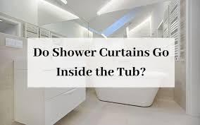 do shower curtains go inside the tub