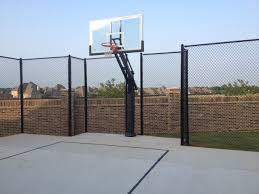 The Pro Dunk Platinum Sits In A Twelve Foot Nook Surrounded By Ball Containment Fencing In Front Of A Brick Wall In The Backyard Of A Residence