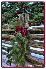 Evergreen Swags Decorating The Fence Along The Lane That Leads To Your Barn Wedding Venue Primitive Christmas Decorating Christmas Decorations Christmas
