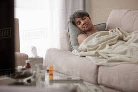Sick mixed race woman laying on sofa - Stock Photo - Dissolve