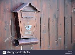 Brown Textured Metal Postbox With A Mail Horn Icon Hanging On A Wooden Fence Concept Of Mailbox And Post Delivery With Copy Space Stock Photo Alamy