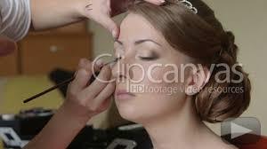 bridal makeup artist applying eyeliner