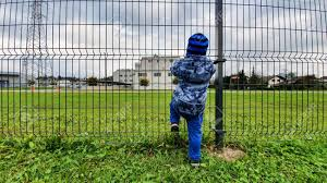 Young Toddler Wants To Escape Home Over The Fence From Kindergarten Stock Photo Picture And Royalty Free Image Image 136214802