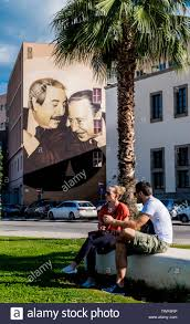 Couple sitting on bench with mural in the background showing ...