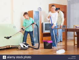 Ordinary family of three with teenager doing housework together in ...