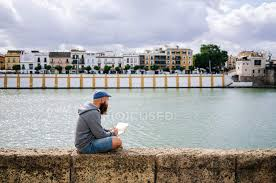 Side View Of Art Student In Casual Clothing Sitting On Rocked Fence Of Quay And Drawing Sketches In Small Album Bay Working Stock Photo 322038766