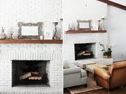 wood mantel on white brick fireplace