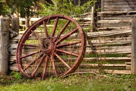 A Single Rustic Wagon Wheel Leaning Against Wooden Fence Stock Photo Picture And Royalty Free Image Image 45965929