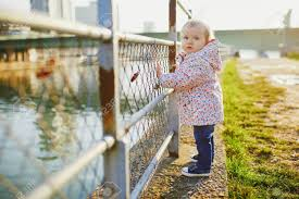 One Year Old Girl Standing Next To Metal Fence In Park Toddler Stock Photo Picture And Royalty Free Image Image 139924869