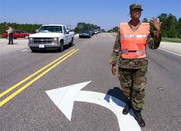 North Carolina Army National Guard Pfc. Latisha Smith helps state police  officers direct traffic.