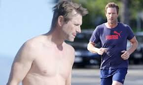 Aaron Eckhart flashes abs as he goes shirtless following run in ...