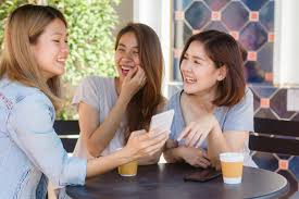 Cheerful asian young women sitting in cafe drinking coffee with ...