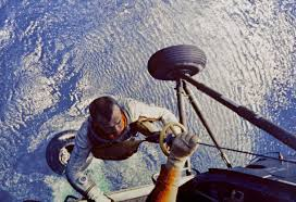 On May 5, 1961, NASA astronaut Alan Shepard piloted his Freedom 7 Mercury  capsule in a 15-minute suborbital flight, becoming America's first astronaut.  In this image, he is shown being hoisted aboard