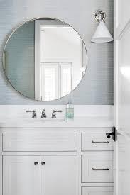 round vanity mirror on blue grasscloth