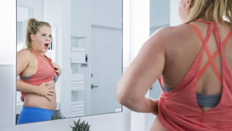 Renee looking in mirror in I Feel Pretty