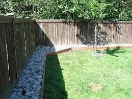 River Rock Fence Border Replacing Bark For A Cleaner Border Small Backyard Landscaping Landscaping Along Fence Sloped Backyard
