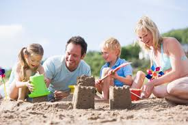 Family on beach making sand castles smiling - HOW Foundation