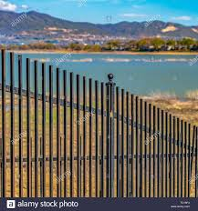 Square Frame Black Metal Fence With A Lake And Grassy Shore In The Background Stock Photo Alamy