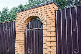Brown Metal Fence Wall With Closed Door And Brick Arch On The Stock Photo Picture And Royalty Free Image Image 152964310