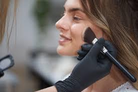 hands of makeup artist contouring face