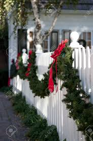 Garland With Red Bows Hanging On White Picket Fence Stock Photo Picture And Royalty Free Image Image 6030848