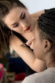 makeup artist applying makeup to young