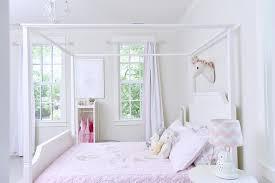 felt unicorn head over white canopy bed