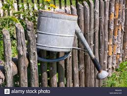 Vintage Watering Can On The Wooden Fence Of A Vegetable Garden Stock Photo Alamy
