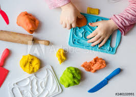 hands with colorful clay child playing