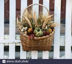 Dried Flower Arrangement In A Wicker Basket Hanging On A White Picket Fence Gate In Colonial Williamsburg Deck The Doors Annual Wreath Competition Stock Photo Alamy