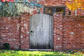 Rustic Wooden Arched Garden Fence In Brick Wall In Autumn With Colored Leaves And Brick House With Colorful Fall Foliage Reflected In Windows Buy This Stock Photo And Explore Similar Images