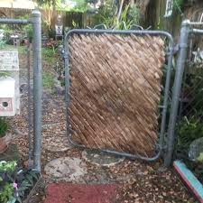 Chain Link Fence Gate Enhanced With Palm Frond Leaves Garden Projects Chain Fence Wood Fence