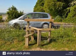 A Fence Step Over Gate In The English Countryside With Car Passing By Stock Photo Alamy