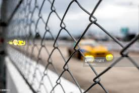 Cars Race Past A Safety Fence Separating The Race Track From Pit Road News Photo Getty Images
