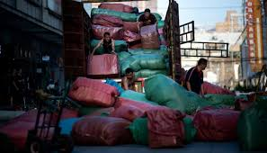 workers unload bags with clothes from a