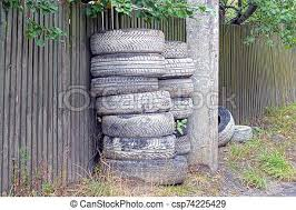 A Pile Of Gray Old Car Tires Near A Wooden Fence On The Street