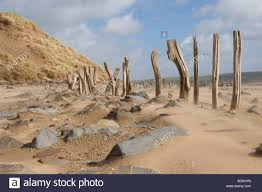 Windswept Beach With Sand Boulders And Derelict Fence Line Showing Stock Photo Alamy