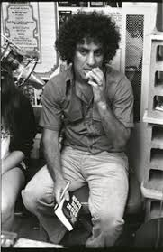 Abbie Hoffman seated at microphone, WBCN studio - Digital Commonwealth