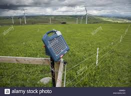 Solar Powered Electric Fence Unit On Pasture With Wind Turbines In Stock Photo Alamy