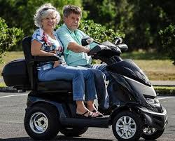 Two people touching on bench style dual mobility scooter