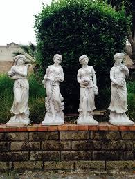 4 concrete garden statues depicting the