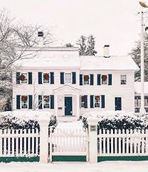 White Picket Fence House New England Snow Christmas Wreaths Hanging On Windows Red Ribbons The Glam Pad