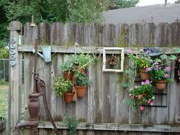 Garden And Patio Old And Rustic Backyard Garden Fence Decoration With Vertical Hanging Planter Pots Ideas Rustic Garden Decor Hanging Garden Backyard Garden