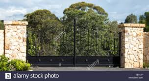 Metal Driveway Rural Property Entrance Gates Set In Sandstone Brick Fence With Eucalyptus Gum Trees In Background Stock Photo Alamy