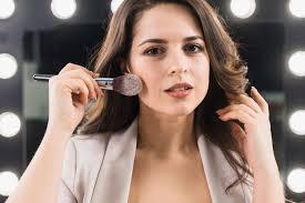 smiling woman applying makeup on mirror