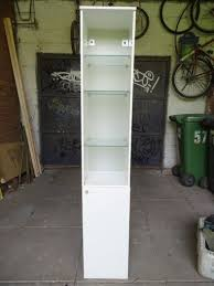 white ikea cabinet w glass shelves for