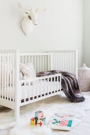 Alyssa Rosenheck White Convertible Crib With Gray Faux Fur Throw Transitional Nursery
