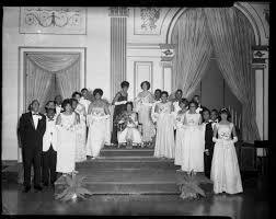 """Group portrait of """"Queen"""" Myra Campbell, seated, being crowned by ..."""