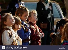 Atsugi, Japan (Nov. 11, 2002) -- Respect for Veterans. Brownie Girl Scouts  from Troop 12, Atsugi, Japan, watch as the Stars and Stripes are raised at  a Veterans Day ceremony on Naval