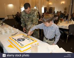 U.S. Army Garrison Wiesbaden Command Sgt. Maj. Larry Addington and Ben  Young, youngest member of the Volunteer Familiy of the year 2016, cut the  cake together at the annual Volunteer Recognition Ceremony